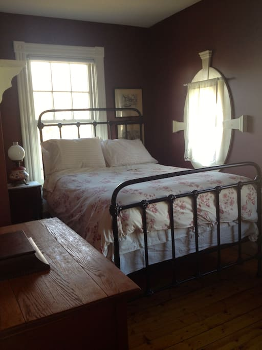 Light filters through antique windows; beautiful, antique double bed