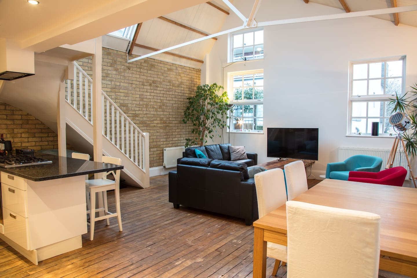 Open plan living space/kitchen with high ceiling and original brickwork