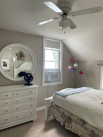 Upstairs bedroom with full size bed, and one twin with air conditioner in window.