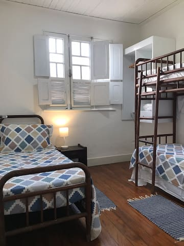 O quarto da frente conta com cama de solteiro e beliche, conjunto de mobília patente que compõe o toque vintage do ambiente.