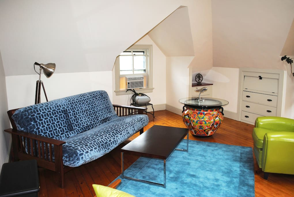 The apartment has a very large common room with a seating area, large desk/working area, and electric fireplace.