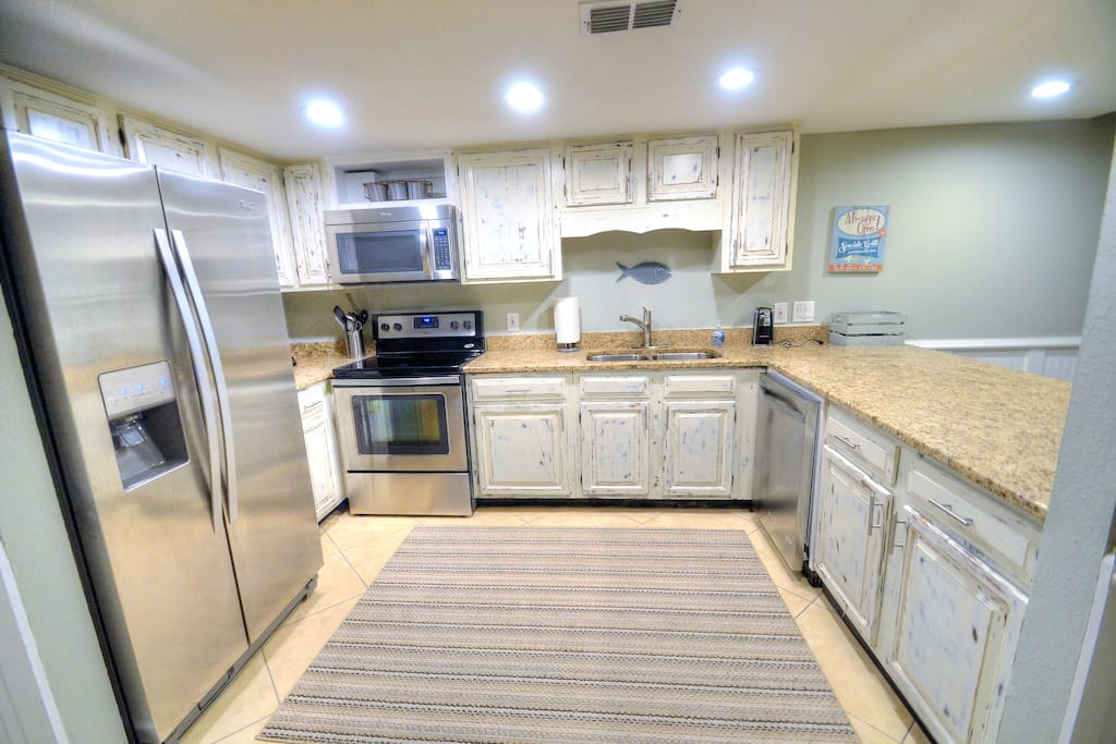 New kitchen with stainless steel appliances, granite counters, and distressed cabinets.