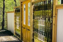 "Come through our "" Bottle Wall"" entrance, crafted from 160 wine bottles! The antique yellow doors from Egypt are eight feet in height!"