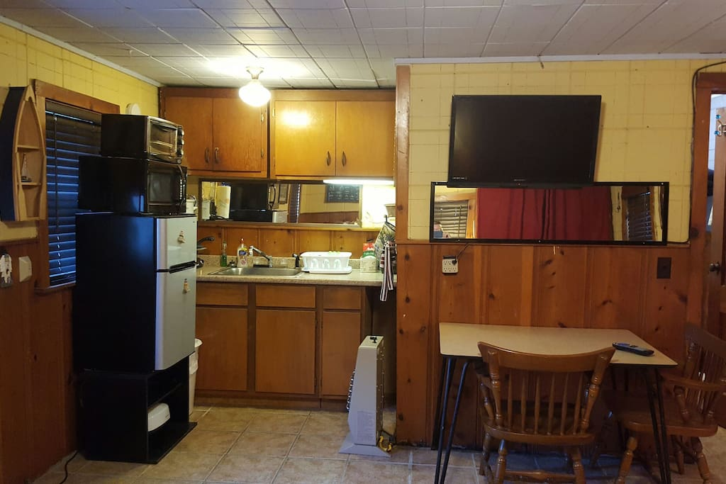 Dishes, silverware, coffee pot, glassware, pans, crock pots, electric skillet, toaster, George Foreman grill, blender,  extra large toaster oven, microwave, coffee, tea, and sugar. 32 inch TV with Dish programming.