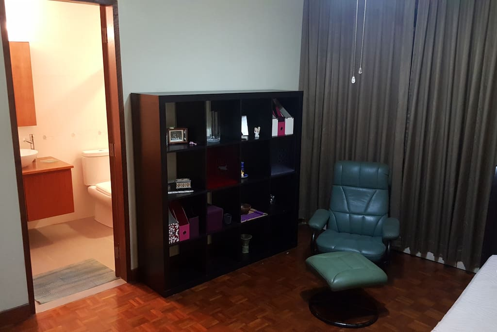 Large open shelving unit, entryway to the master bathroom and a comfortable reclining chair.