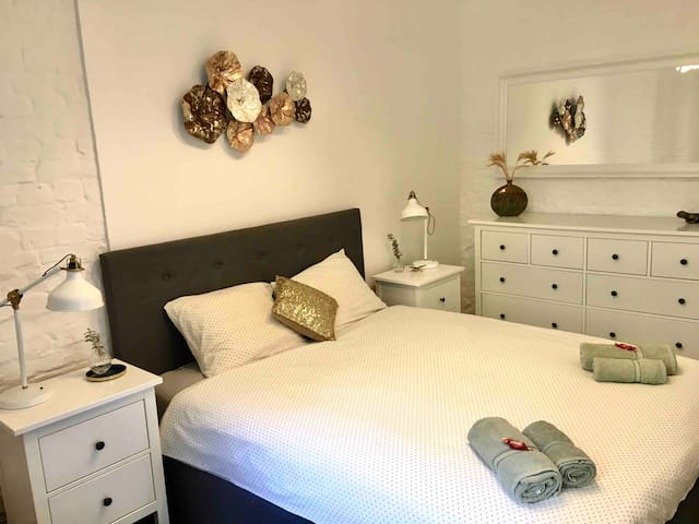 Light bedroom with a comfortable double bed and sun-blocking shades