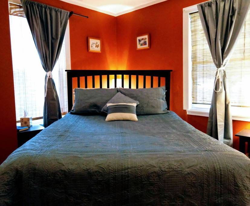 Queen bed, closet, tables with lamps, floor lamp, freestanding fan, chair, light blocking curtains.