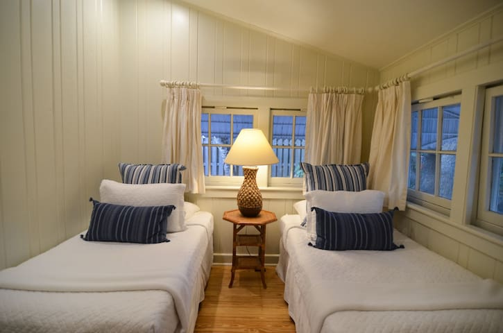Light airy twin bedroom with large windows and 2 beds draped in crisp white linens