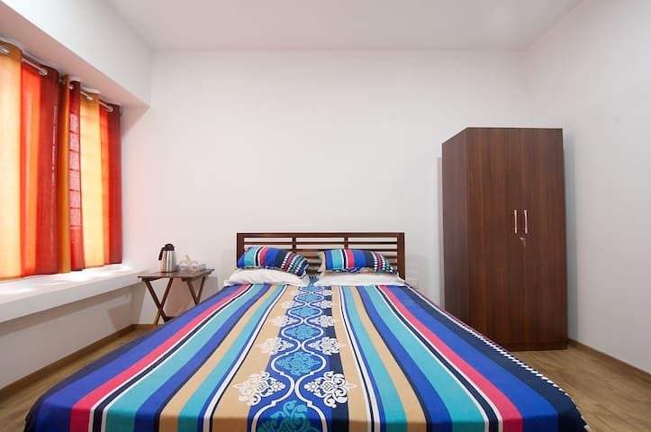 Spacious room with a Queen bed, AC, WiFi and TV