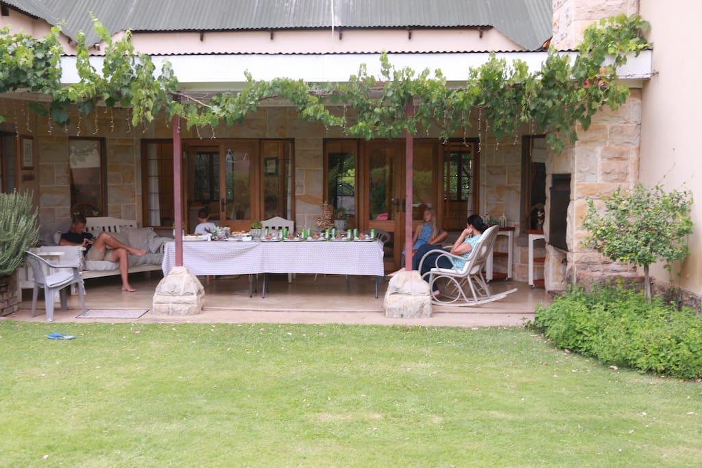 Relaxing stoep with braai overlooking swimming pool and vineyard.