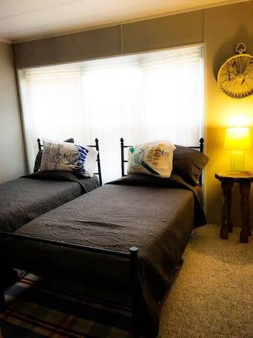 Smaller bedroom with twin beds and attached bathroom.