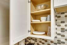 Mixing bowls, plates and bowls are just some of the items in this fully stocked kitchen.