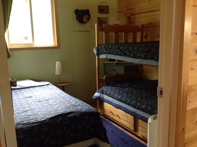 """Middle bedroom-""""Moose/Bear Room"""" has 3 beds. A twin bed and twin/ twin bunk. Dresser with mirror, as well as under bed  drawers for storage."""