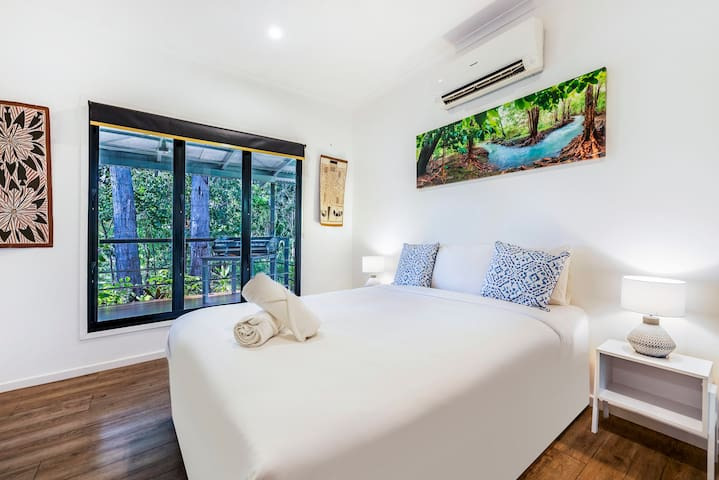 A cosy bedroom has luxe black-out blinds, external cupboards and a plush queen bed; and has direct access to the outdoor deck