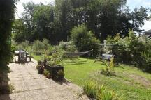 Le jardin de devant, avec terrasse, hamac et balancelle pour la détente.