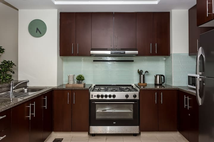 An integrated kitchen made of dark wood and incorporates all the necessary items for a carefree stay