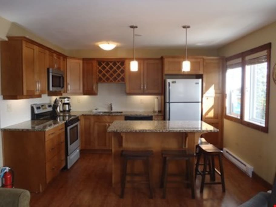 The fully-equipped kitchen features granite countertops and stainless steel appliances.