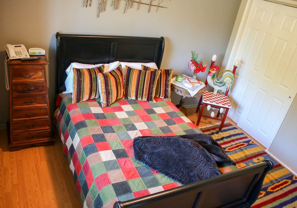 Bedroom with a double bed,  hard wood floors, TV and closet