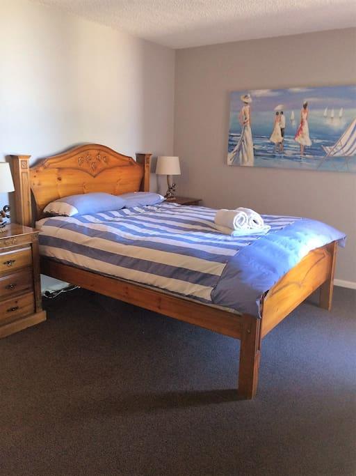 Bedroom 1 has Queen bed, walk-in robe & private balcony overlooking Glenelg Beach
