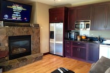 Living room/kitchen area and fireplace.