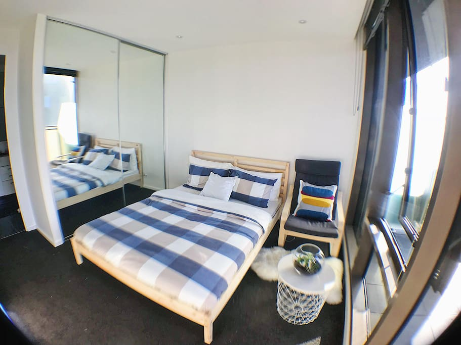 Spacious bedroom with king bed, built-in wardrobe, armchair and little coffee table.