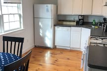 Kitchen with dishwasher, stove, refrigerator, coffee maker, microwave, toaster oven.