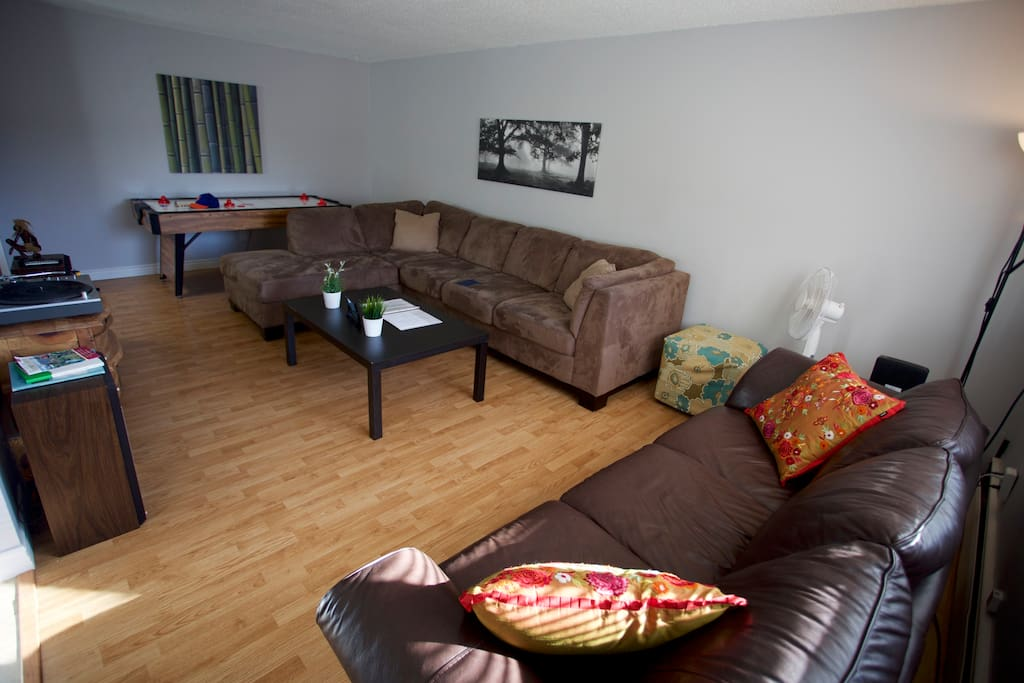 Living room with 1 large sectional and 1 leather couch.