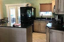 The kitchen equipped with granite counter top, refrigerator, range stove, microwave, dishwasher, and island.