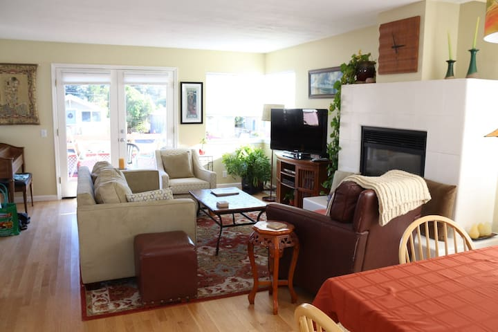 Open living room with dining area, gas fireplace, French doors to large wood deck