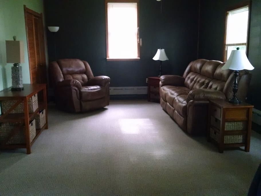 "Family room with new carpet and power reclining sofa 46"" flat screen television with cablevision and WIFI."