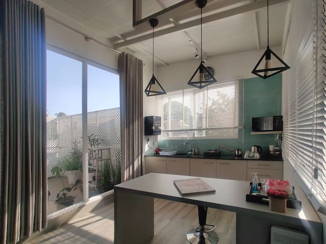 Click of the wall less penthouse from the bed area. U can see the couch, work table and kitchen. Through the huge french windows Outside u can appreciate the sun and the plants.