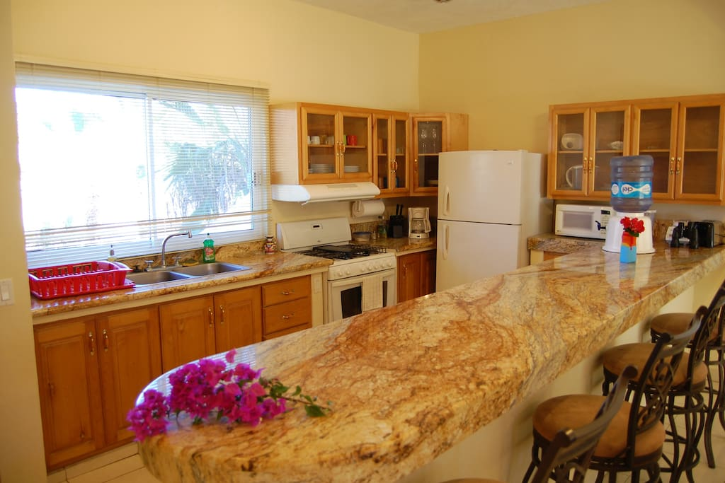 There is a large kitchen with all appliances and utensils.