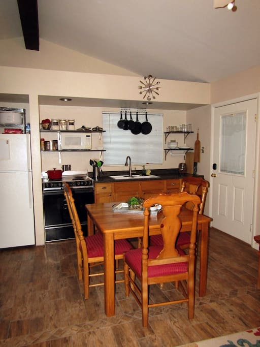 Kitchen w/full size fridge, stove, sink, microwave. Pots and pans and dinnerware included.