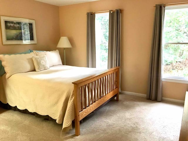 This spacious bedroom suite has one queen sized bed, suitable for two people, and a private bathroom with double sinks. Two large windows provide light and  a view of the back yard woods.