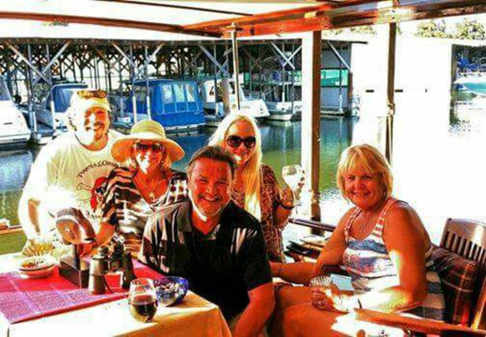 Friends enjoying the aft deck which is approximately 30 square feet feet of teak decking and mahogany cabinet with bar, sink, refrigerator wine rack and storage. The deck is covered and electricity both AC/DC.