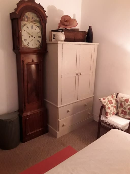 The grandfather clock and vintage cupboard in the main bedroom.
