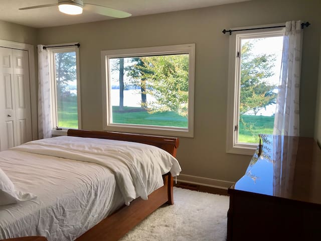 Main level bedroom with queen bed & gorgeous river views. Beautiful custom made Italian wood furniture.  Large dresser, end table, lamp, large closet and ceiling fan.