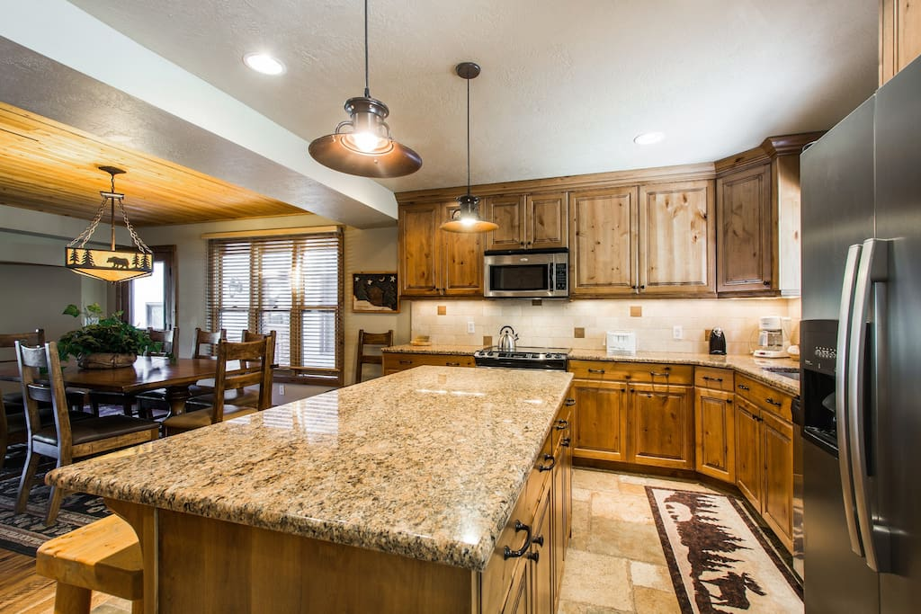 The kitchen is beautifully finished with thick granite countertops, hardwood cabinetry and a large kitchen island, which can also second as a breakfast bar with bar stool seating for four (4) people.