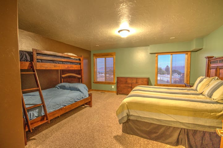 Upstairs bedroom with a king and twin over full bunk beds with a view of the lake