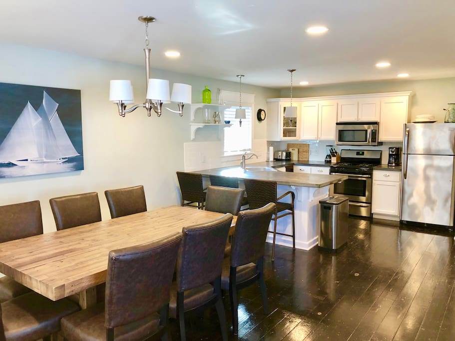 View of Dining Table and Beautiful Kitchen with Stainless Steel Appliances and Concrete Counters