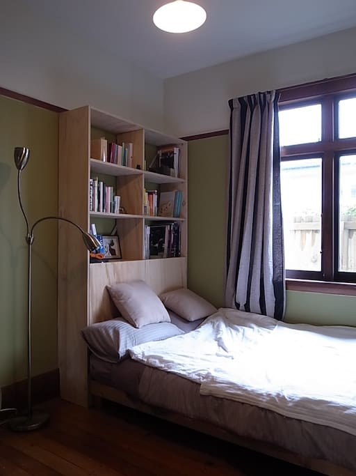 Your bedroom, with new bookshelf, small double bed and morning sun.