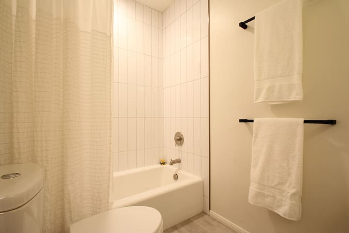 Common bathroom with tub/shower combination (shower head on opposite end from tub spout)