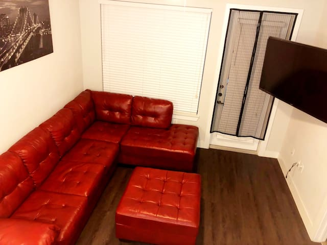 """Modern living room area with 70"""" HD Television"""