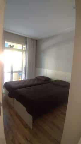 Vista do quarto existente no andar inferior com armário embutido instalado, além de uma cama de solteiro e uma bicama.