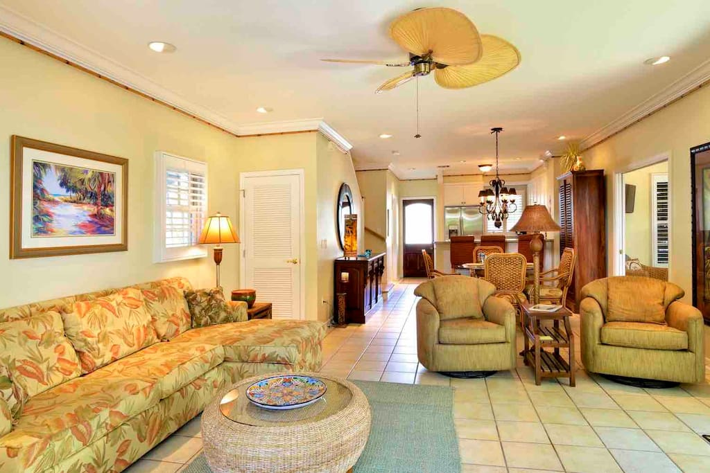 The living room has comfortable seating for everyone and unique overhead fan...
