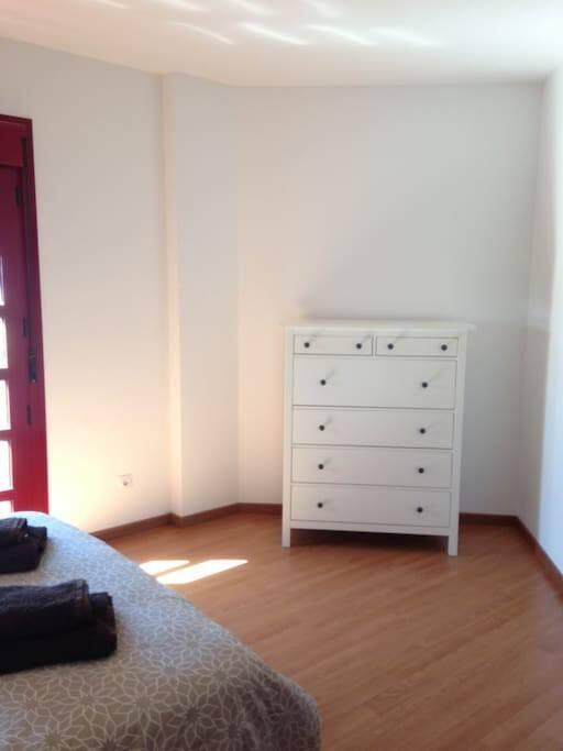 El dormitorio cuenta con un cómoda cajonera y un perchero.