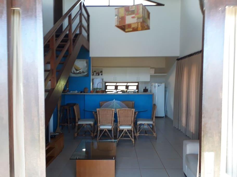 Vista sala e cozinha com geladeira, fogão, utensílios doméstico e escada com acesso ao solariumo.