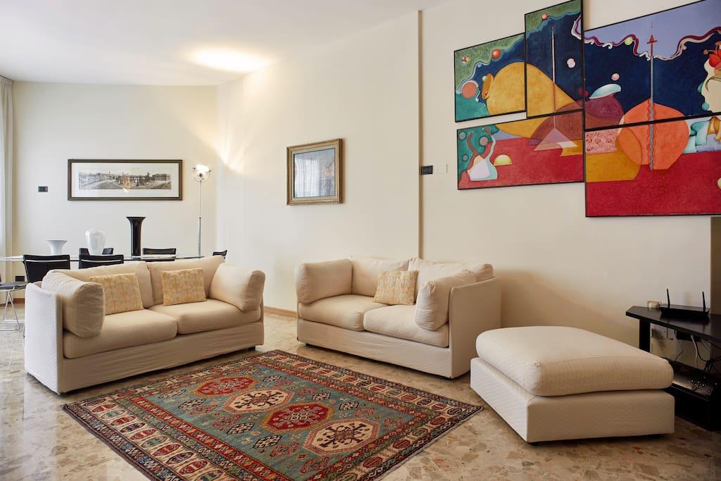Ampio salone luminoso con balcone. Large sunny living room with balcony. Grosses helles Wohnzimmer mit Balkon.