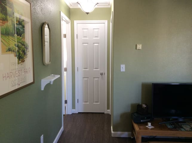 New flooring and fresh paint throughout.  Shelf for phones and USB outlets below, and linen closet. Bathroom door to the right, bedroom door to the left.
