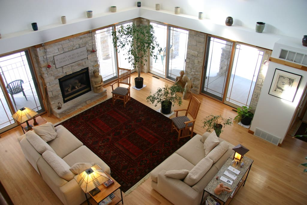 The Great Room with a fireplace surrounded by windows.